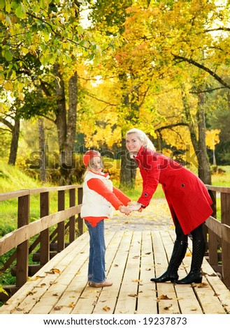 Mother and daughter relaxing outdoors - stock photo