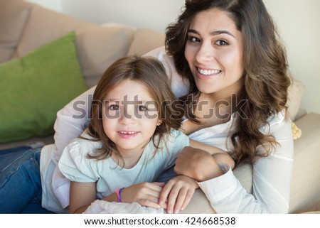 Mother and daughter relaxing together on couch - stock photo