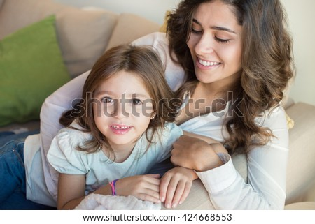 Mother and daughter relaxing together on couch