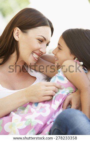 Mother and Daughter relaxing together outisde - stock photo