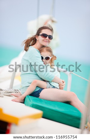 Mother and daughter relaxing while sailing on a luxury yacht - stock photo