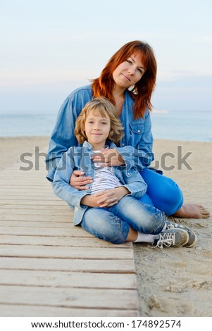 mother and daughter resting near the sea - focus on the mother - stock photo