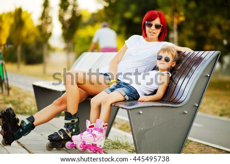 Mother and daughter resting on the bench in park after rollerblading.  - stock photo