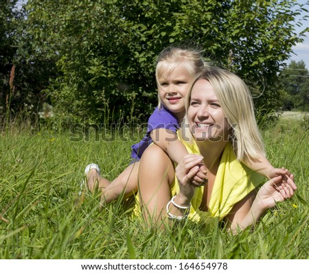 mother and daughter resting on the grass
