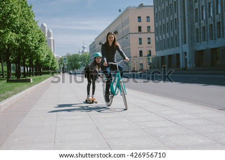 Mother and daughter ride a scooter and bicycle together - stock photo
