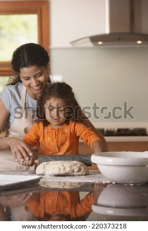 Mother and daughter rolling bread dough - stock photo