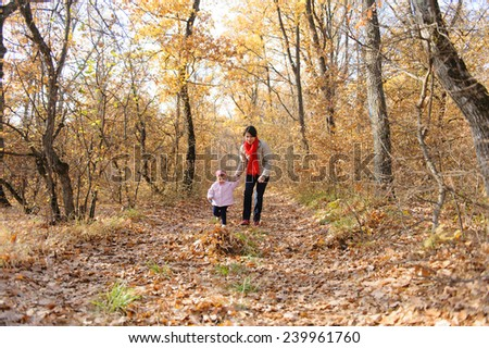 mother and daughter running in forest