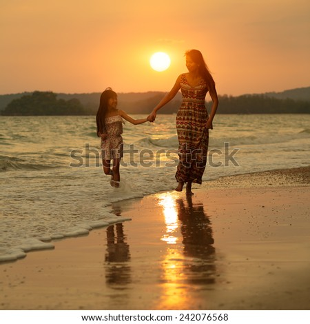 Mother and daughter running on the beach with sunset - stock photo