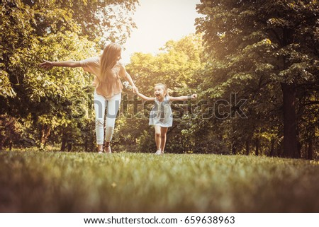 Mother and daughter running trough meadow. Mother and daughter holding hands.