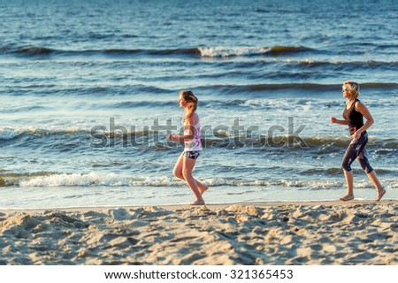 Mother and daughter runs In the Baltic Sea