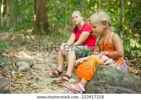 Mother and daughter seat on stones rest on break at hiking trail to mountain top - stock photo