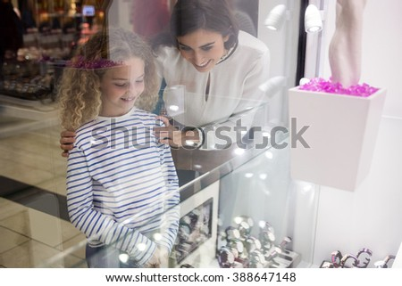 Mother and daughter selecting a wrist watch from a display of watches in shop - stock photo