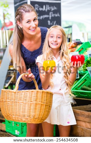 Mother and daughter selecting vegetables while grocery shopping in organic supermarket