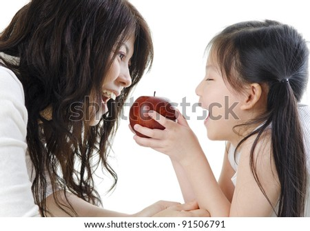 Mother and daughter sharing an apple on white background - stock photo