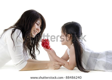 Mother and daughter sharing grapes on white background - stock photo