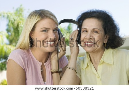 Mother and Daughter Sharing Headphones - stock photo