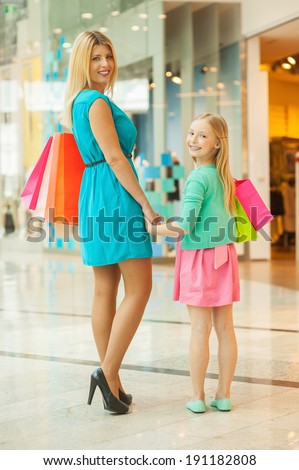 Mother and daughter shopping. Cheerful blond hair mother and daughter holding shopping bags and looking over shoulder while standing in shopping mall - stock photo