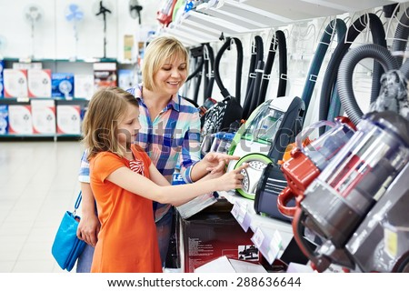 Mother and daughter shopping for electric vacuum cleaner, smiling - stock photo