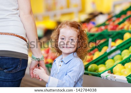 Mother and daughter shopping for fresh fruit in a supermarket holding hands as the little girl pauses to look back at the camera