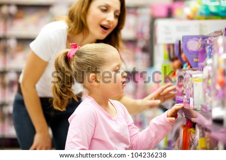 mother and daughter shopping for toys - stock photo