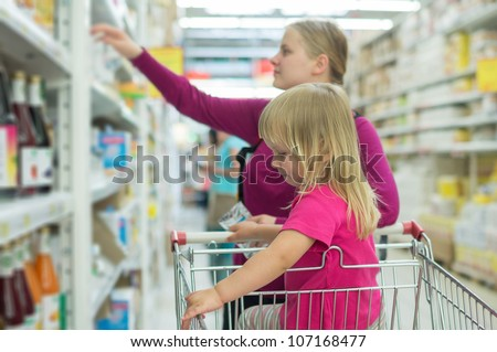Mother and daughter shopping in juice section in supermarket