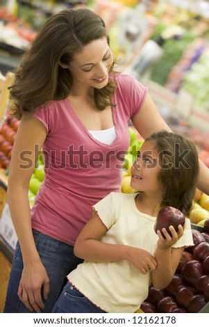 Mother and daughter shopping in produce section of supermarket - stock photo