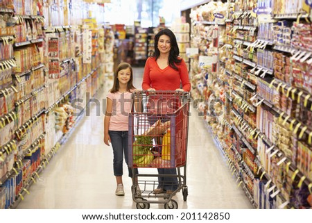 Mother and daughter shopping in supermarket - stock photo