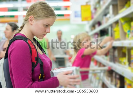 Mother and daughter shopping in tea and coffee section in supermarket