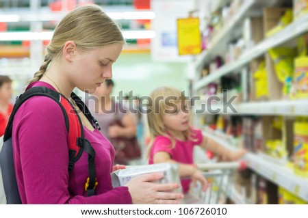 Mother and daughter shopping in tea and coffee section in supermarket - stock photo