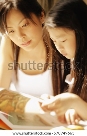 Mother and daughter, side by side, going through magazine