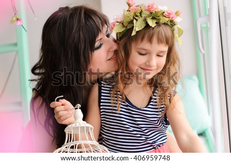 Mother and daughter sit near the window and my mother said something to the girl's ear - stock photo