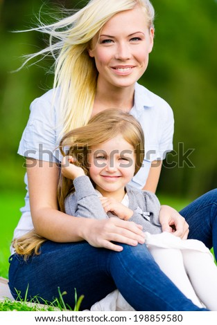 Mother and daughter sit on the grass embrace each other. Leisure time of happy family - stock photo