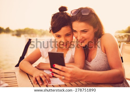 Mother and daughter sitting at cafe and looking at smart phone - stock photo