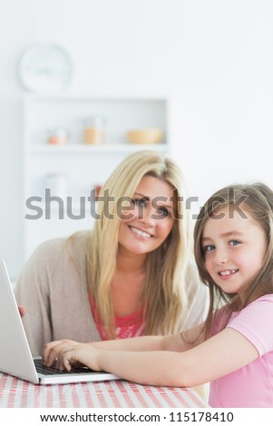 Mother and daughter sitting at the kitchen while smiling with a laptop together