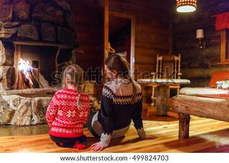 Mother and daughter sitting by a fireplace in their family home on winter