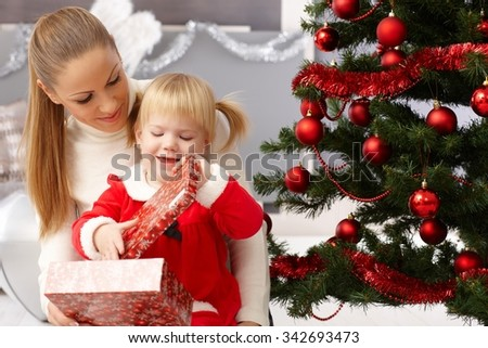 Mother and daughter sitting by christmas tree, opening presents.