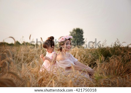 mother and daughter sitting in a field of rye.  - stock photo