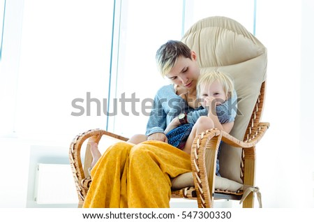 Mother and daughter sitting in a rocking chair. Indoor photo on the background of a large bright window.