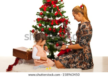 Mother and daughter sitting in front of Christmas tree in their home - stock photo