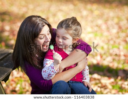 Mother and daughter sitting on a bench in the fall - stock photo