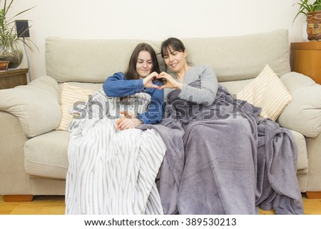 Mother and daughter sitting on a couch forming a heart with her hands