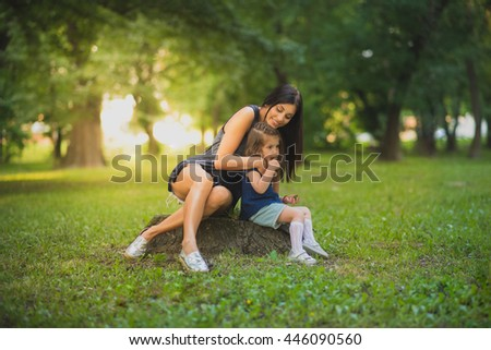 Mother and daughter sitting on a stump in a park on a beautiful day