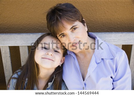 Mother and daughter sitting on bench - stock photo