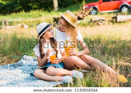 mother and daughter sitting on blanket at picnic, looking at each other and holding glasses of juice