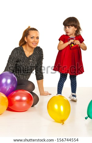 Mother and daughter sitting on floor with balloons - stock photo