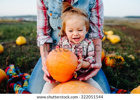 Mother and daughter sitting on pumpkins, Halloween eve