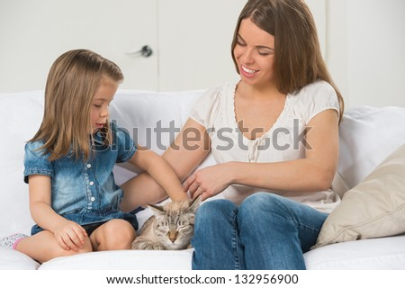 Mother and daughter sitting on sofa and cuddling cat - stock photo