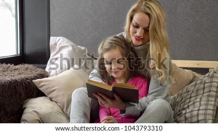 Mother and daughter sitting on the bed in an embrace and reading a book.