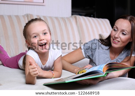 Mother and daughter sitting on the couch and read a book - stock photo