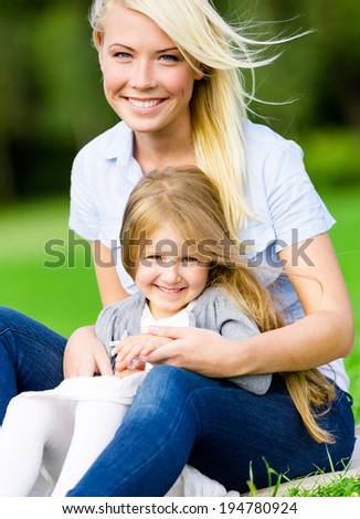 Mother and daughter sitting on the green grass embrace each other. Leisure time of happy family - stock photo